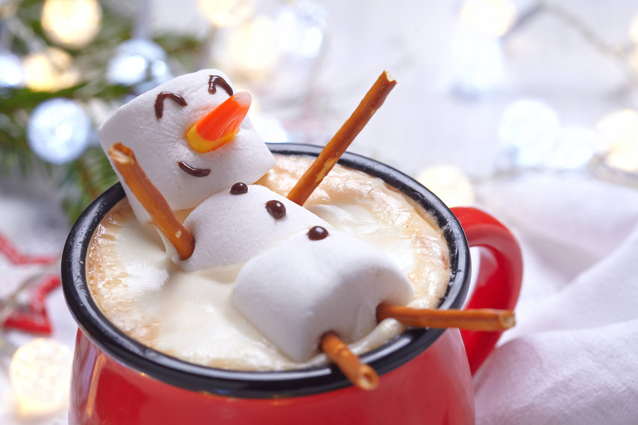 Snowman made of marshmallows in cup of hot chocolate