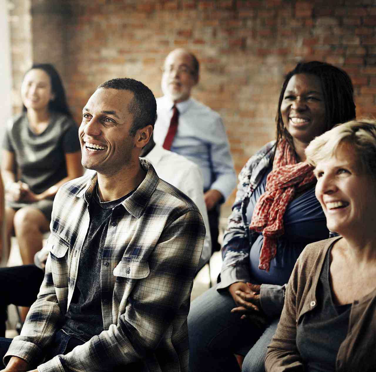 Group of people listening to and smiling at an unseen speaker.