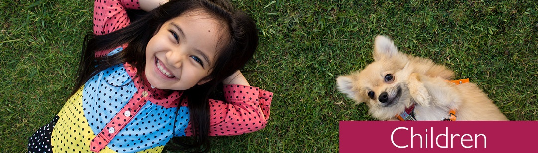 Image of small girl and dog laying in grass
