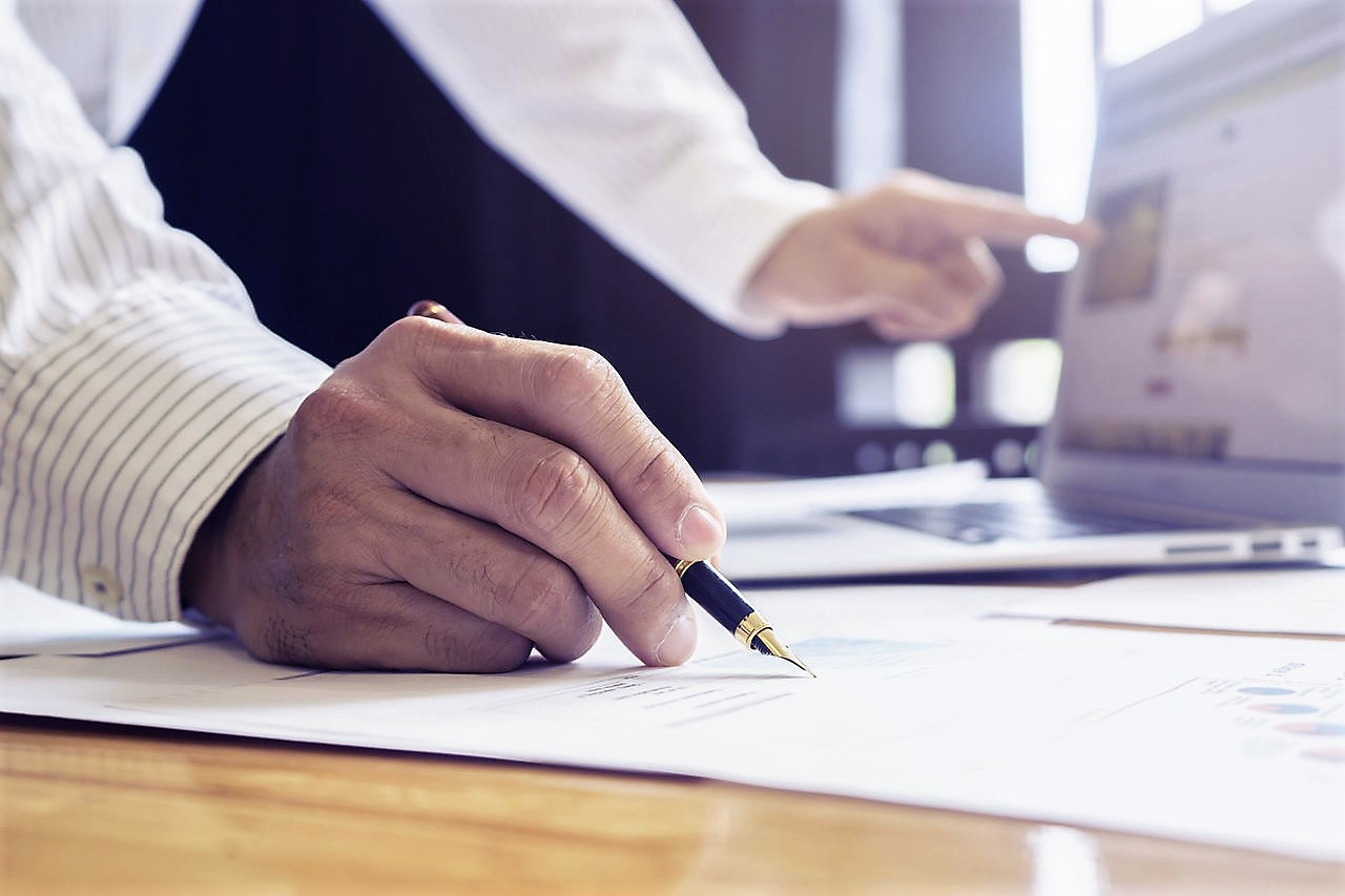 Businessman's hand holding a fountain pen, signing documents