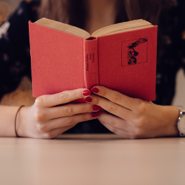 Girl's hands holding open a red book