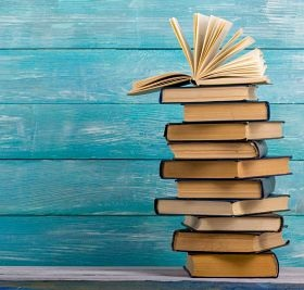 blue wooden background with a stack of books on the right