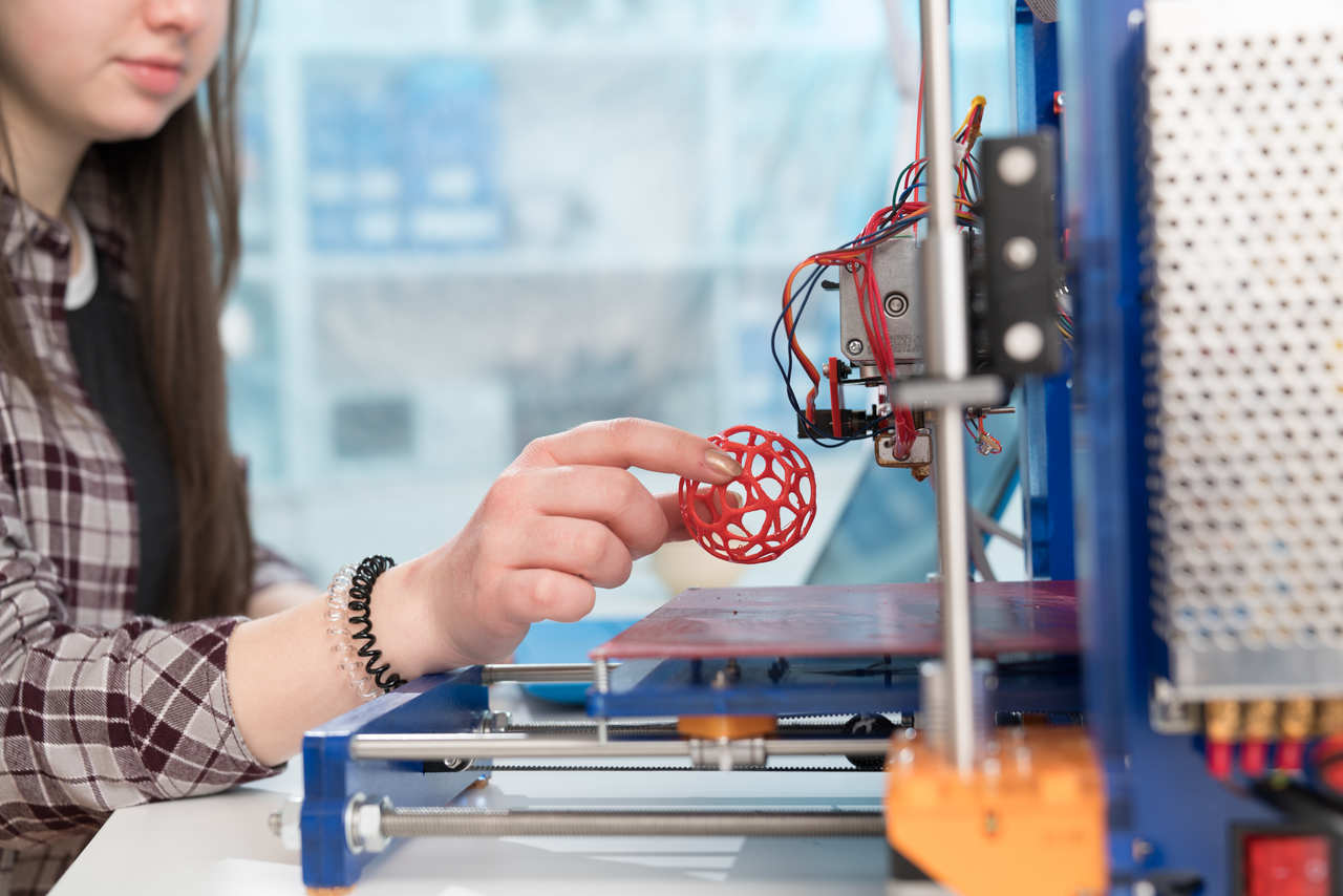 Girl removing red sphere from 3D printer